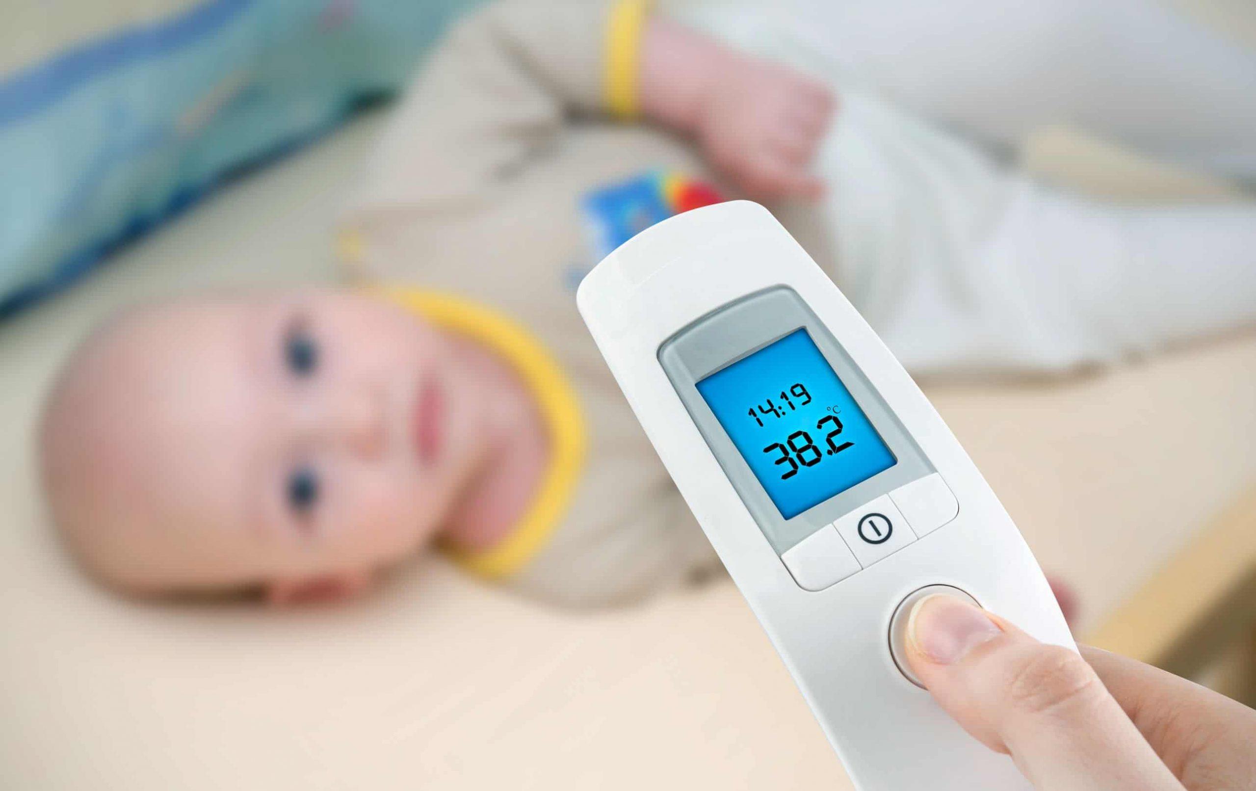 Na foto uma pessoa segurando um termômetro digital na frente de um bebê deitado.