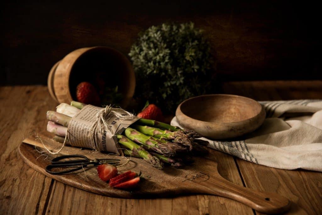 Na foto aspargos e morangos em cima de uma tábua de madeira com um cenário de pote e hortaliças ao fundo.