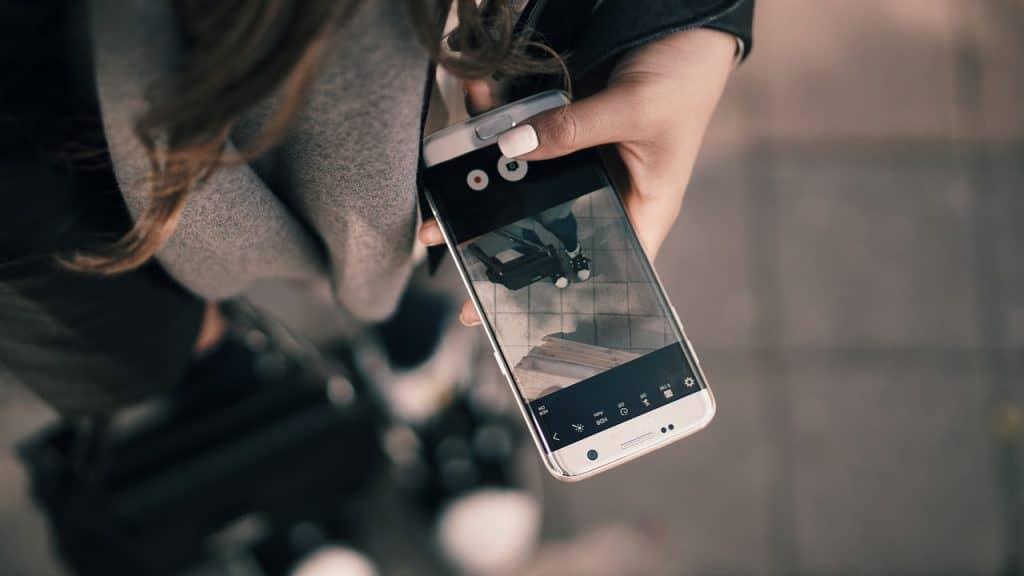 Imagem de uma mulher configurando a câmera de um smartphone.