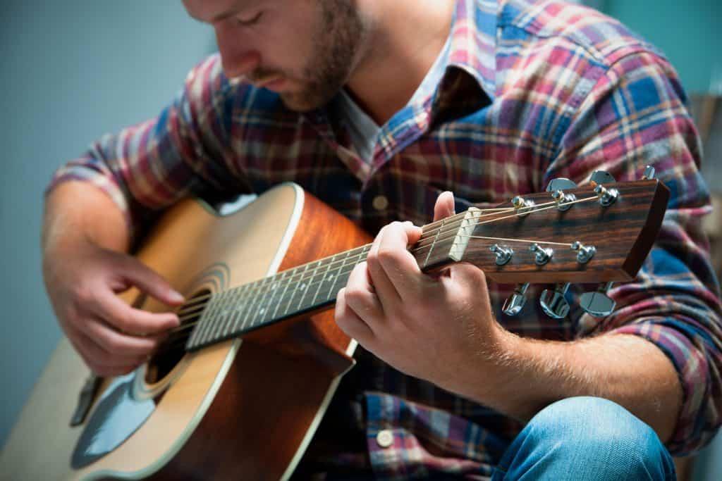 Um homem tocando um violão.