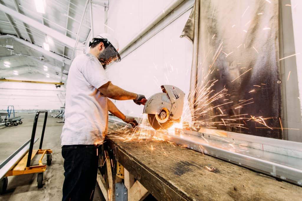 Imagem mostra um homem com equipamentos de proteção trabalhando no corte de uma peça de metal.