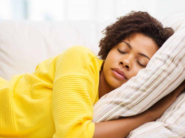 Mulher dormindo sobre travesseiro.