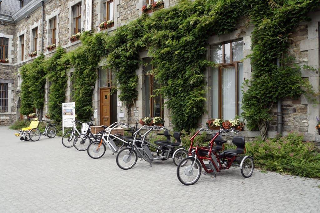 Triciclos e bicicletas estacionados em frente a um estabelecimento.