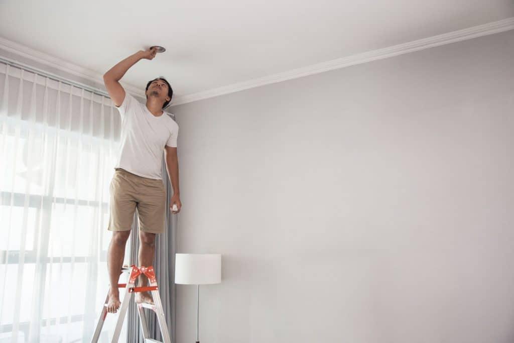 Imagem mostra um homem fazendo reparo no teto com uma escada de alumínio.