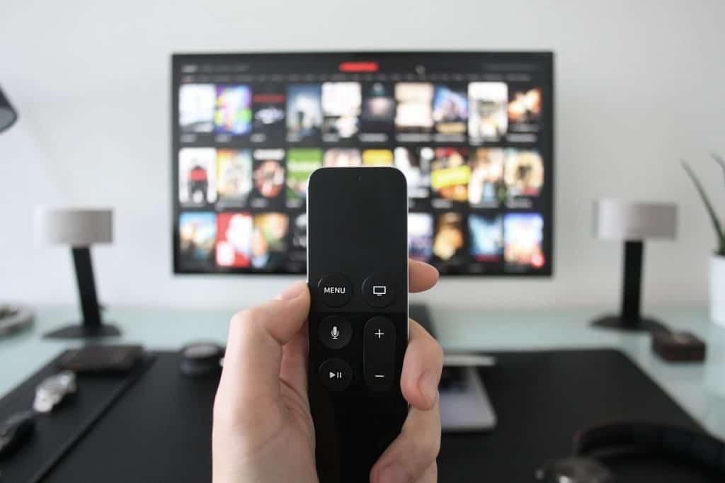 Foto que mostra uma mão segurando um controle remoto, e, ao fundo, uma smart TV conectada a um aplicativo, em cima de uma mesa.