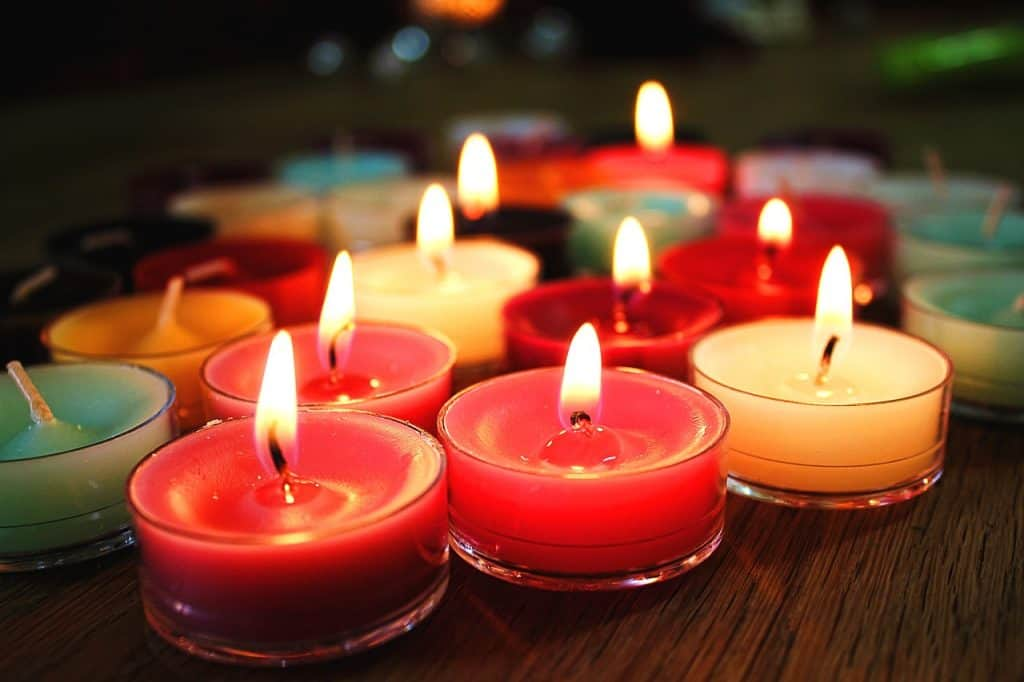 Imagem de velas aromáticas vermelha, brancas e verdes sobre mesa de madeira.