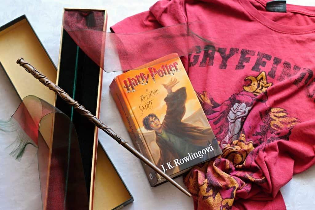 Imagem da varinha da Hermione Granger ao lado de um livro e uma camiseta do Harry Potter.