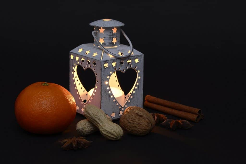 Imagem de vela aromáticas em lanterna decorativa com laranja, nozes, anis estrelado e canela.
