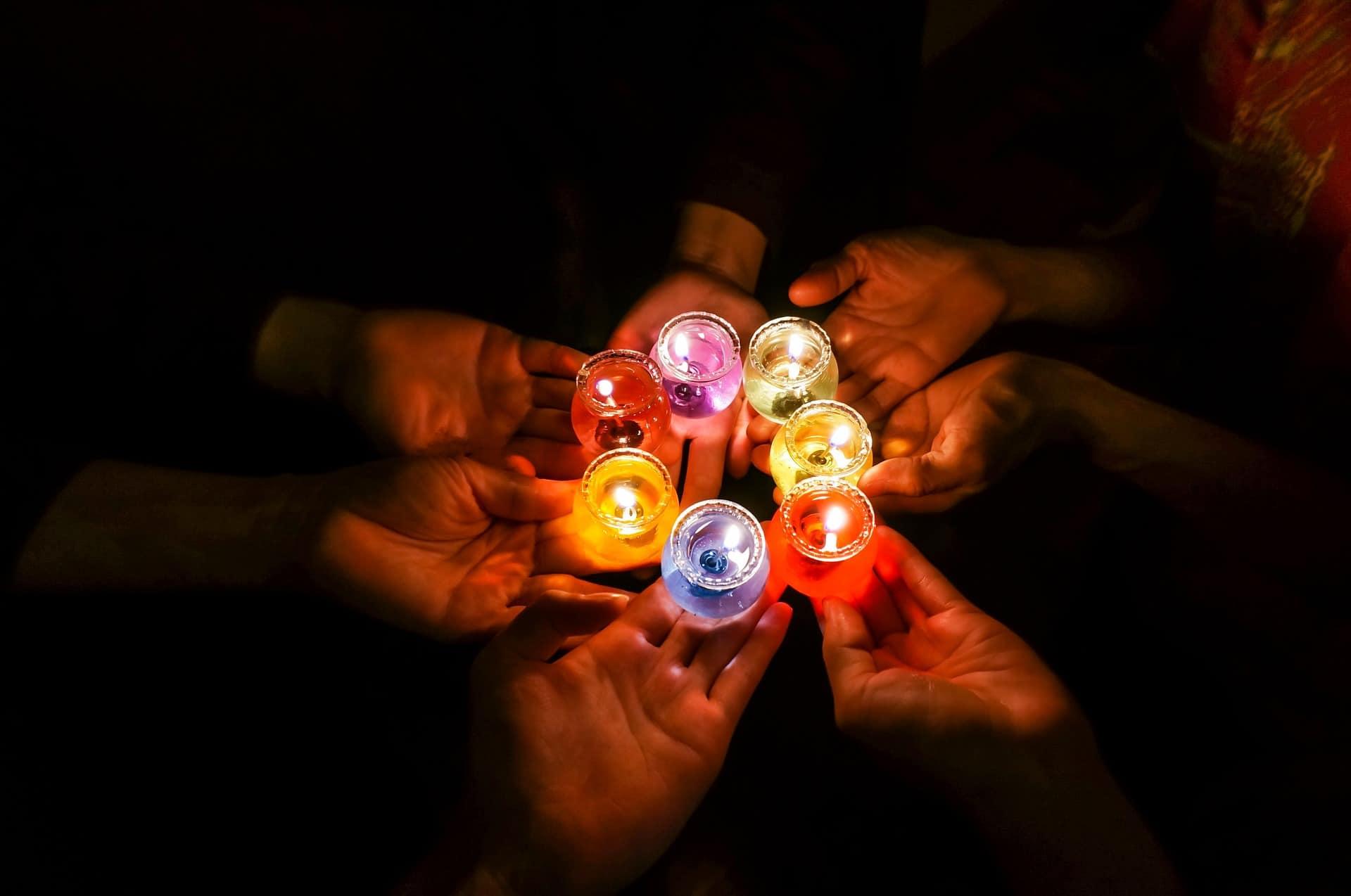 Imagem de pessoas segurando velas aromáticas coloridas acesas no escuro.