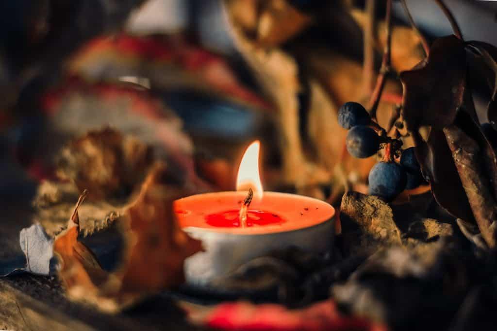 Imagem de vela aromática vermelha em meio a decoração outonal com folhas secas.