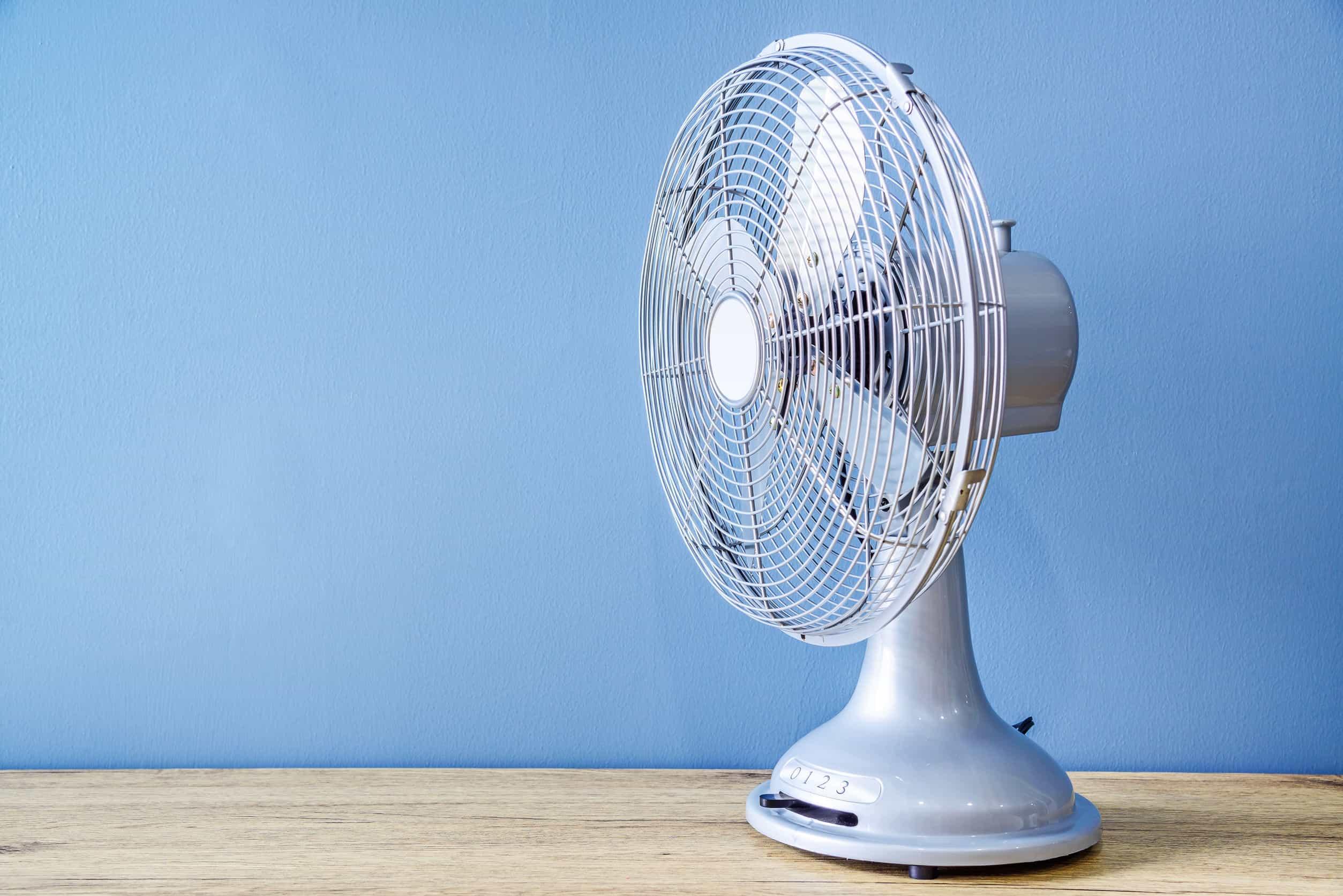 Na foto um ventilador em cima de uma superfície de madeira em frente a uma parede azul.