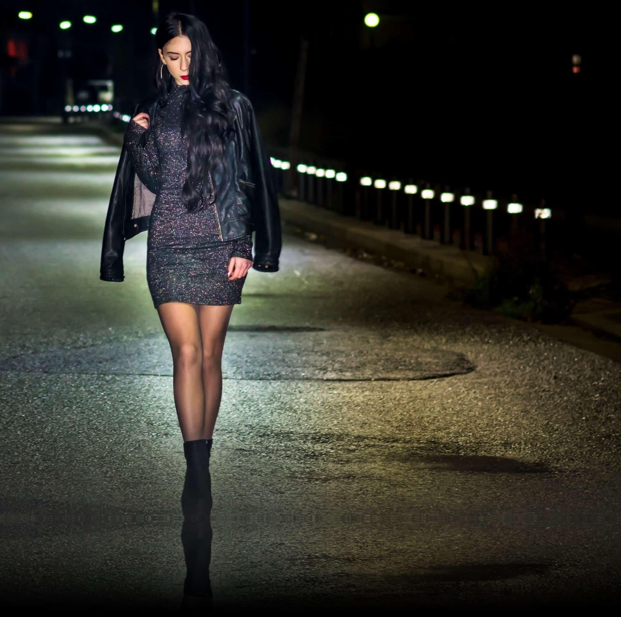 Foto de uma mulher de botas de salto alto, vestido brilhoso e jaqueta de couro preta andando em uma rua escura. Ela está olhando pra baixo, com parte dos cabelos jogados para frente.