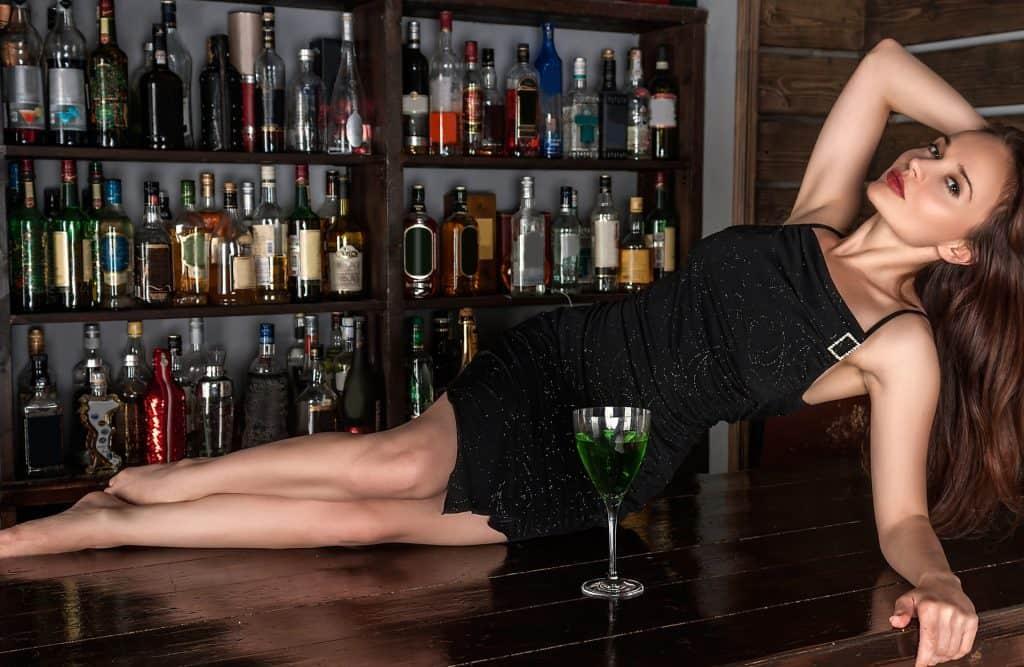 Imagem de mulher com vestido preto segurando bebida em cima de balcão.
