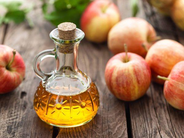 Vinagre de maçã e maçãs ao redor.