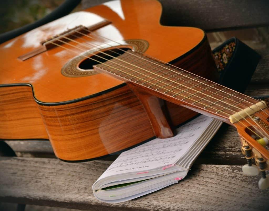 Um violão e um livro de música com partituras musicais estão em cima de um banco de madeira.