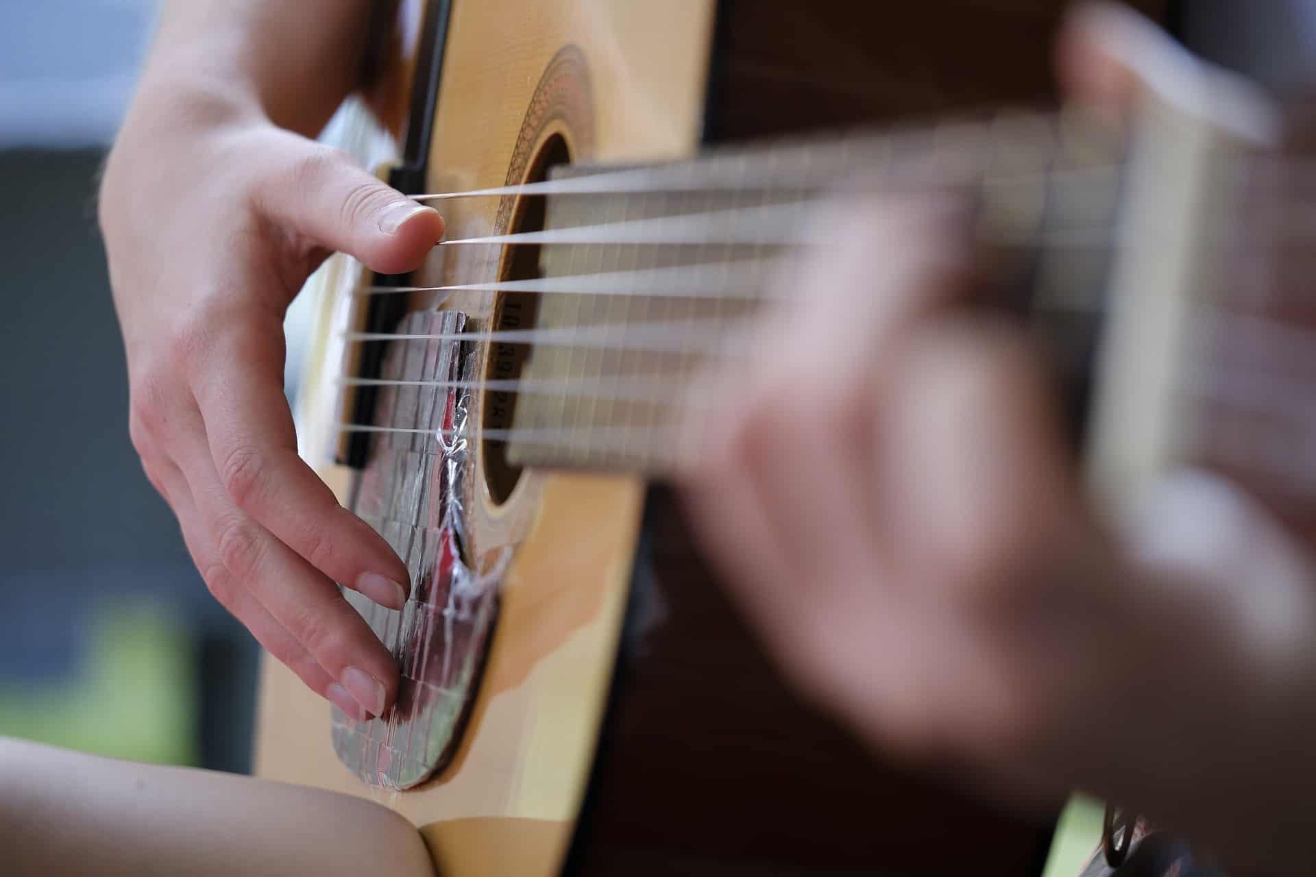 Close de uma mão tocando violão.