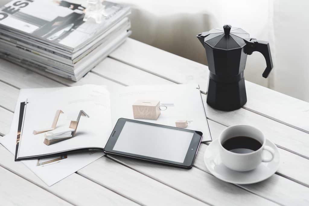 Na foto um tablet em cima de uma revista ao lado de um xícara com café e uma jarra.