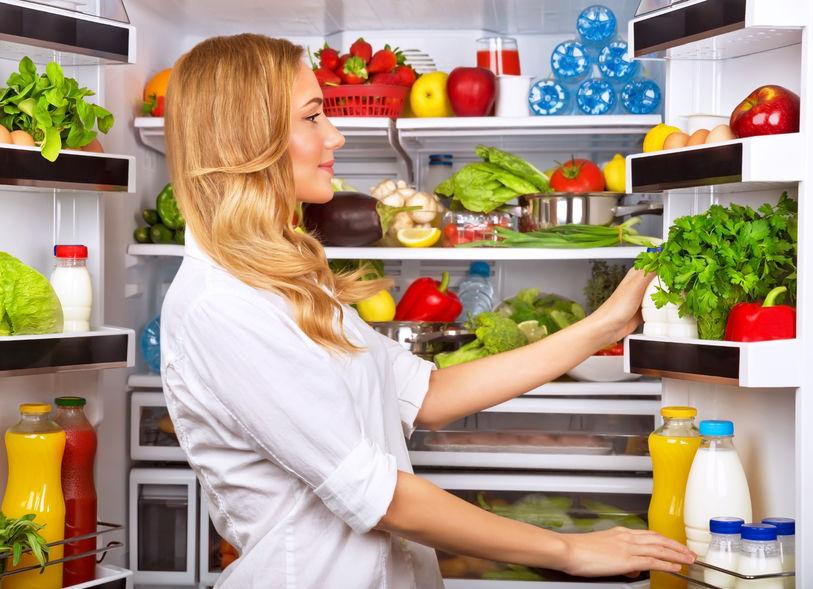 Imagem de uma mulher olhando os alimentos na geladeira.