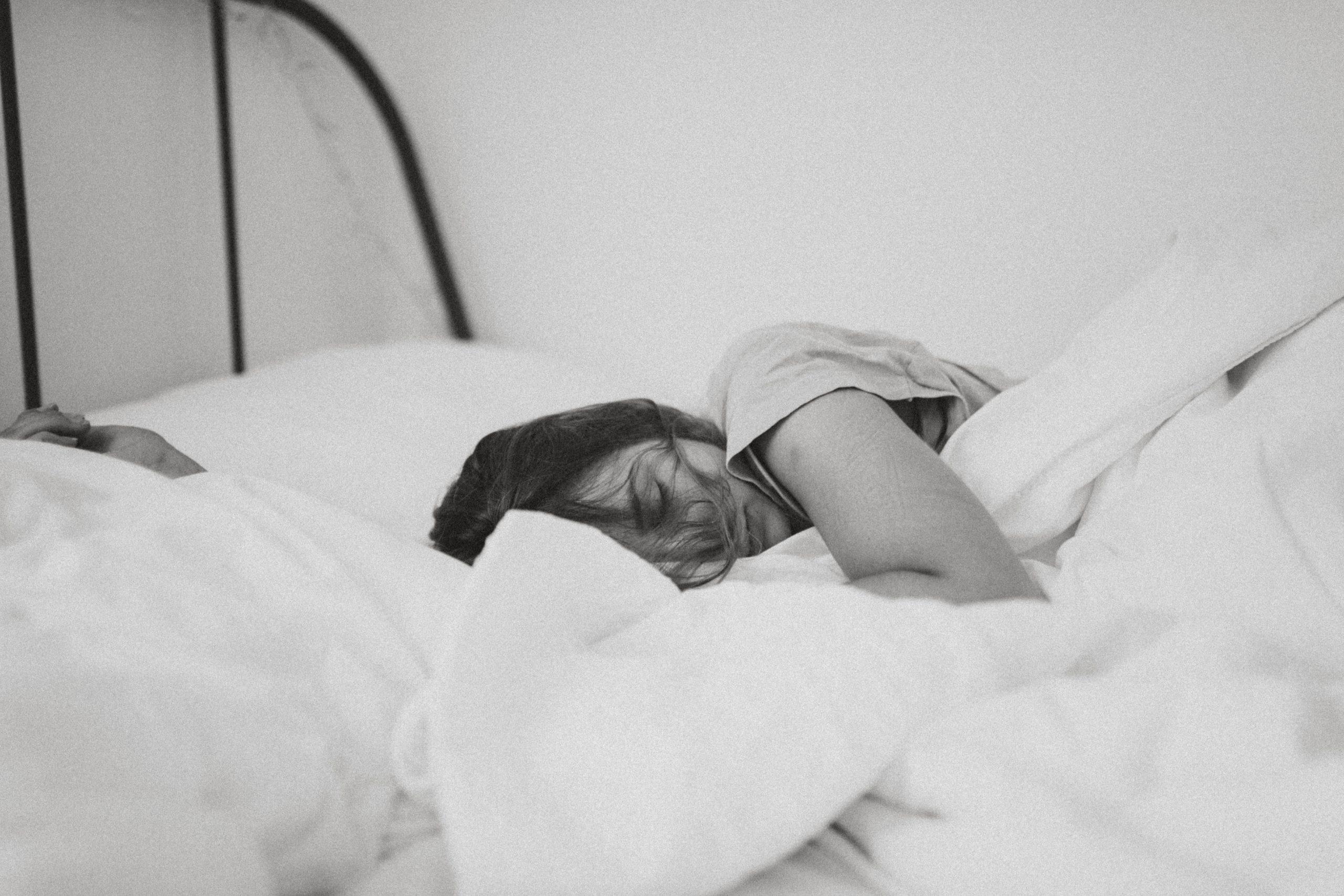 Imagem mostra uma mulher dormindo, deitada de lado numa cama com muitas camadas de roupa de cama e travesseiros.