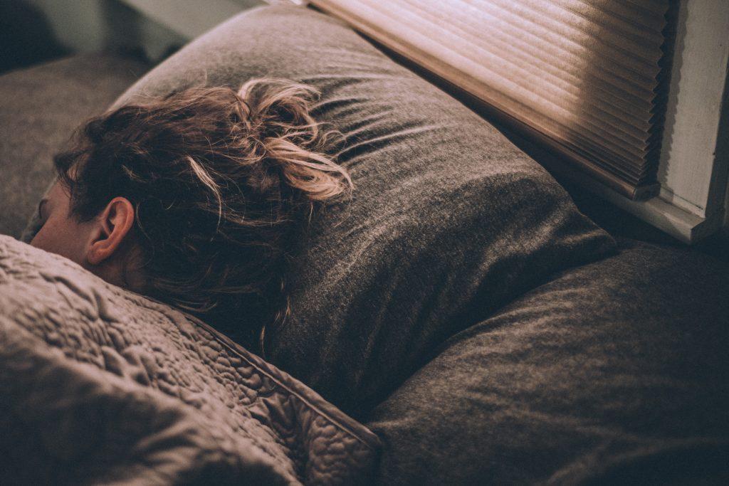 Imagem mostra uma mulher dormindo numa posição lateral e sorrindo.