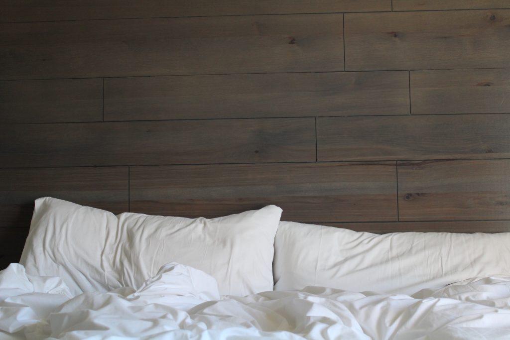 Imagem mostra dois travesseiros recentemente usados, com amassos, sobre uma cama bagunçada.