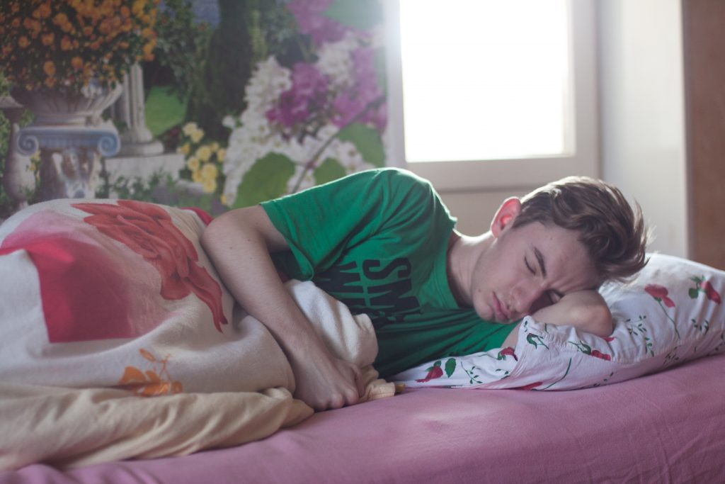 Imagem mostra um rapaz dormindo num travesseiro comum, deitado de lado apoiando os braços entre sua cabeça e o travesseiro.