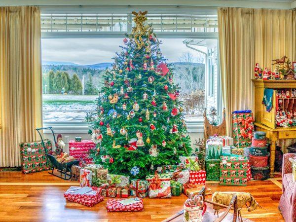 Na foto está uma árvore de Natal no meio de uma sala com presentes.