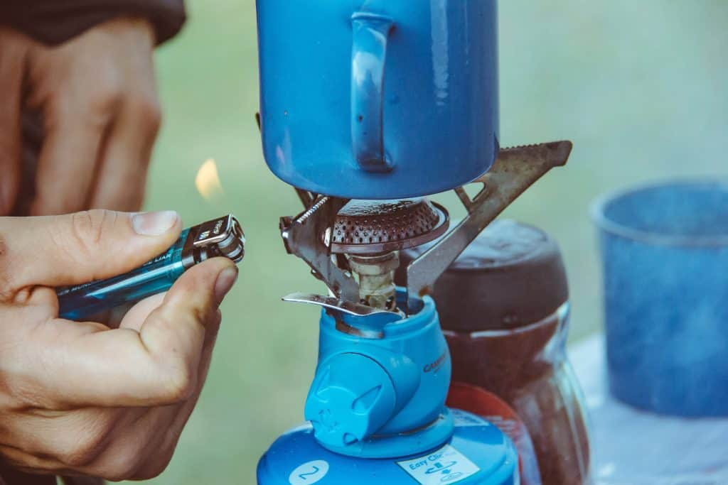 Mão usando isqueiro para acender fogaréu em acampamento.