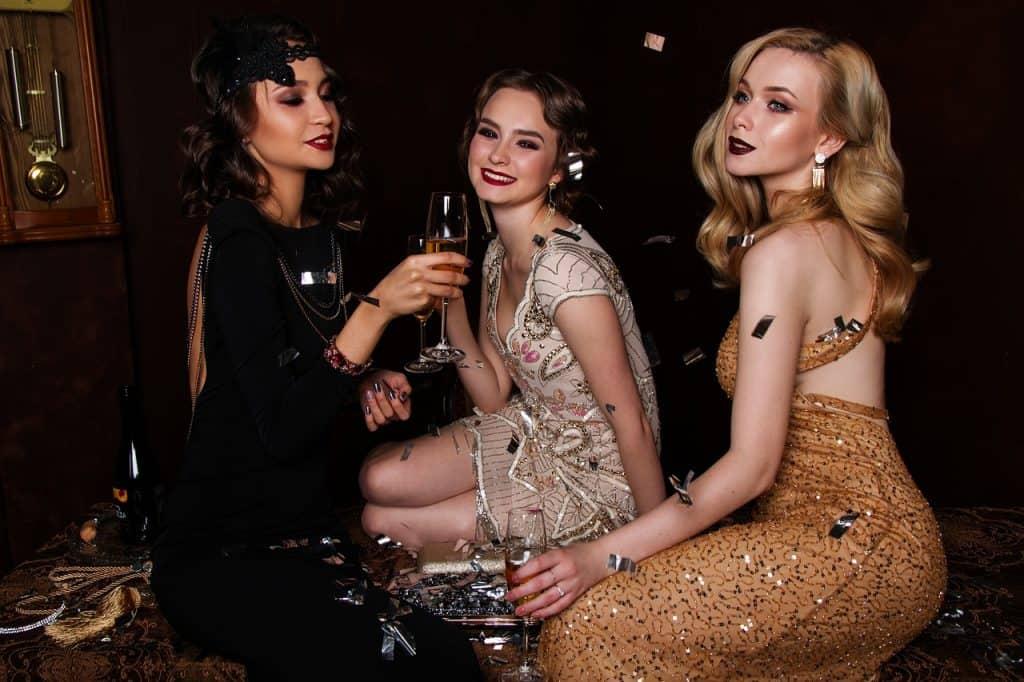 Na foto três mulheres de vestido de festa sentadas.