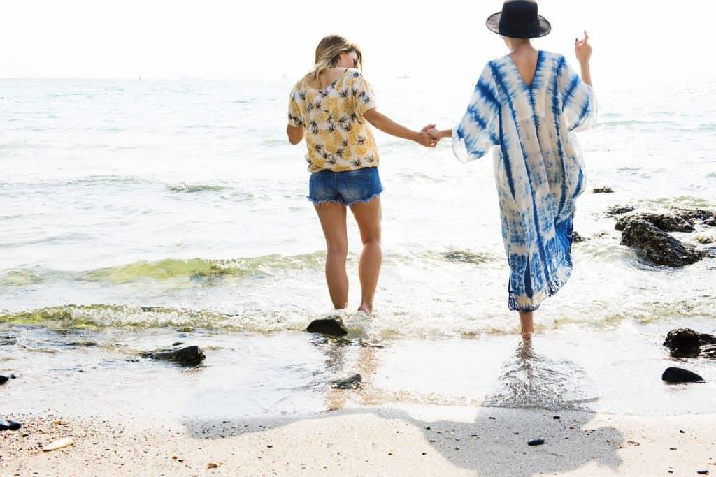 Duas mulheres com saída de praia caminhando na beira da praia.
