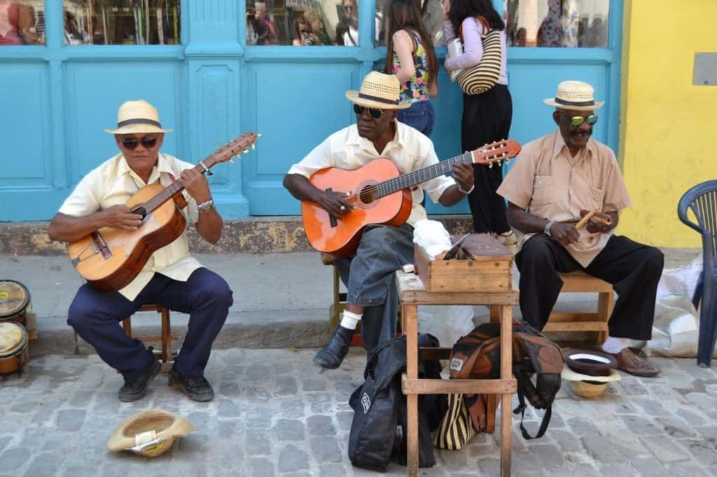3 elderly men.  Two play the guitar.  The other plays a small percussion instrument.  In the center of the image there is a wooden bench with guitar covers stored below.