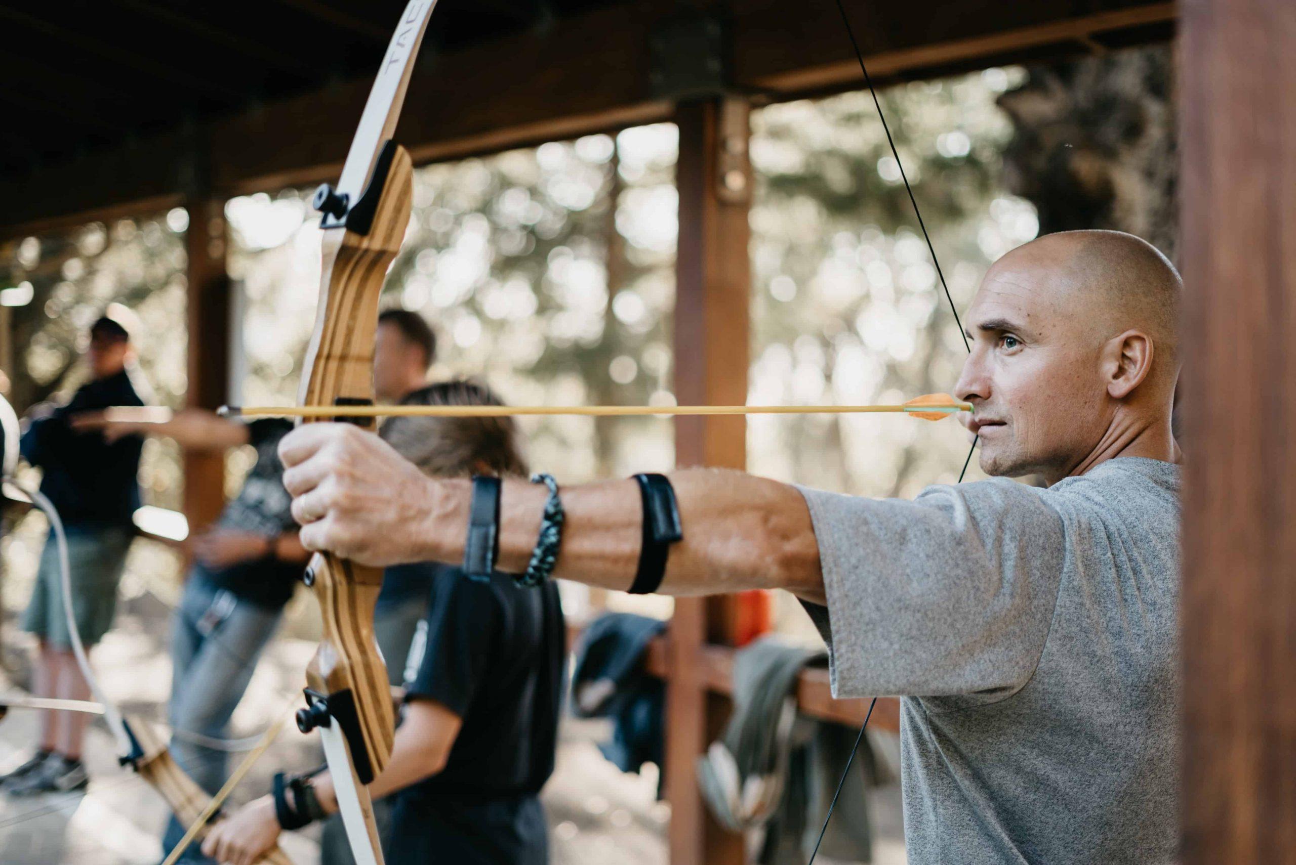 Homem segurando arco e flecha.