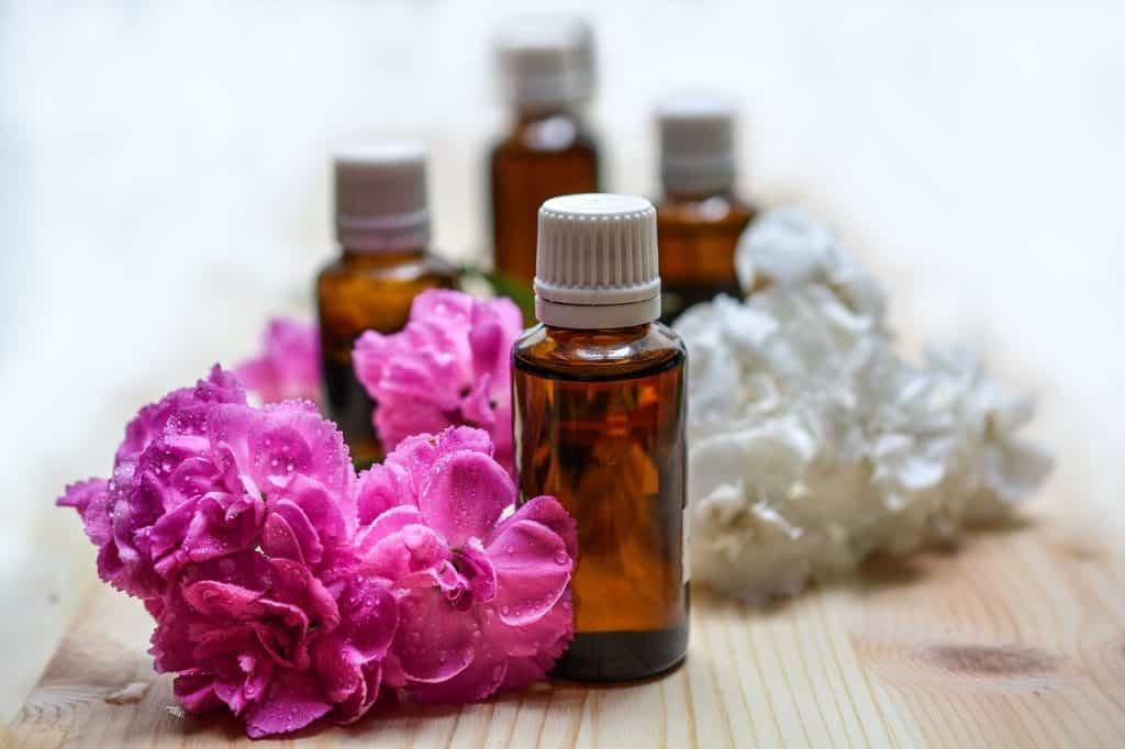 Imagem de frasco de óleo essencial e flores utilizados nas fórmulas de desodorantes íntimos.