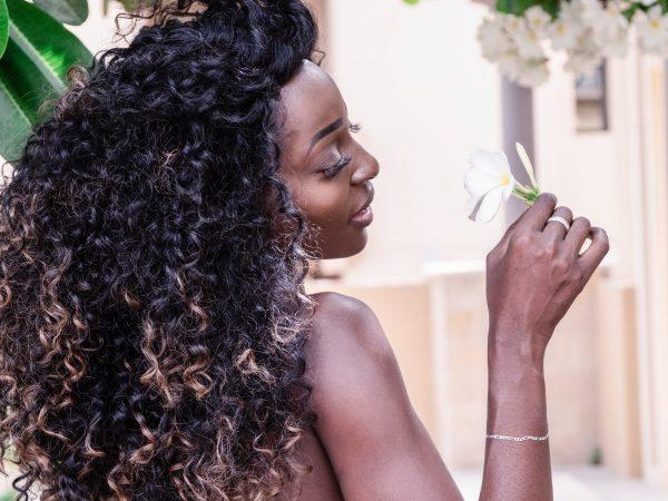 Foto de mulher negra, de costas, mas com cabeça virada para o lado, de cabelos cacheados, segurando uma flor branca.