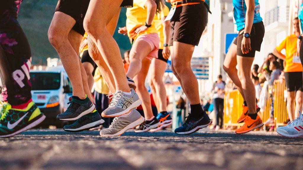 Destaque de pernas de corredores com tênis Asics.