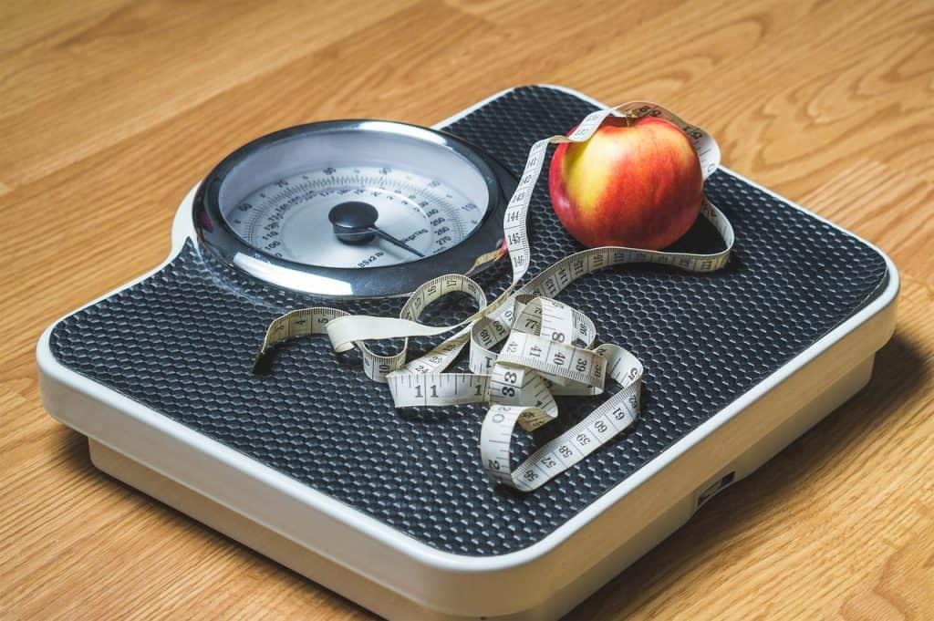 Balança, fita métrica e maçã.
