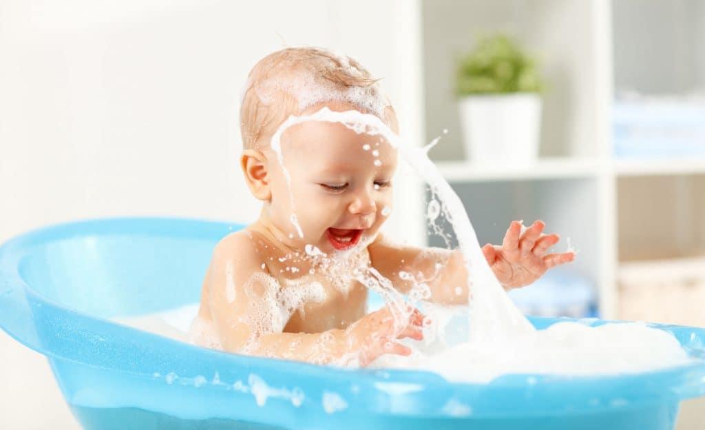 Imagem de bebê tomando banho em uma bacia com espuma.
