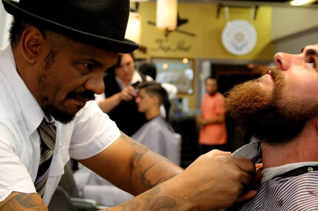Barbeiro barbeando homem.