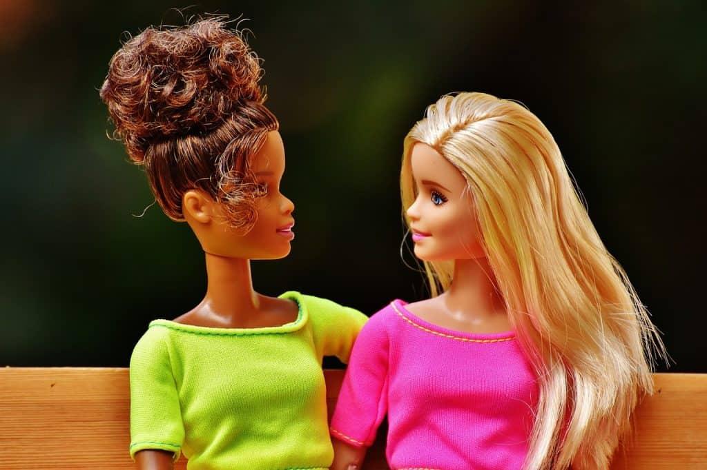 Uma barbie loira com blusa rosa e uma morena com blusa verde.