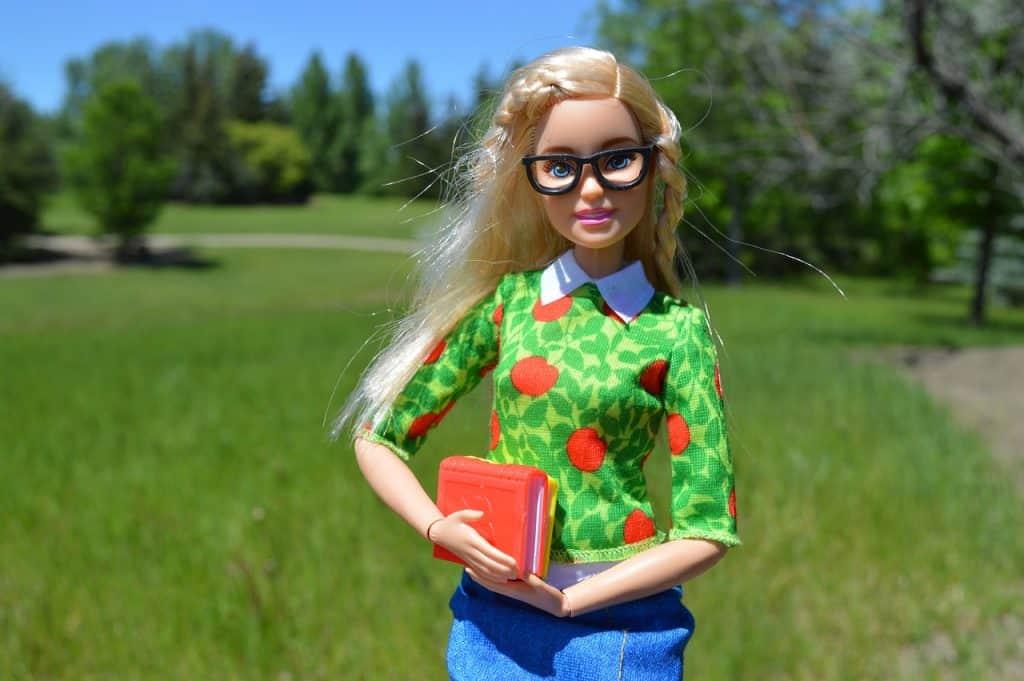 Barbie estudante usando óculos e segurando livros em um gramado.