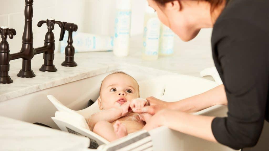 Imagem de uma mãe dando banho em um bebê.