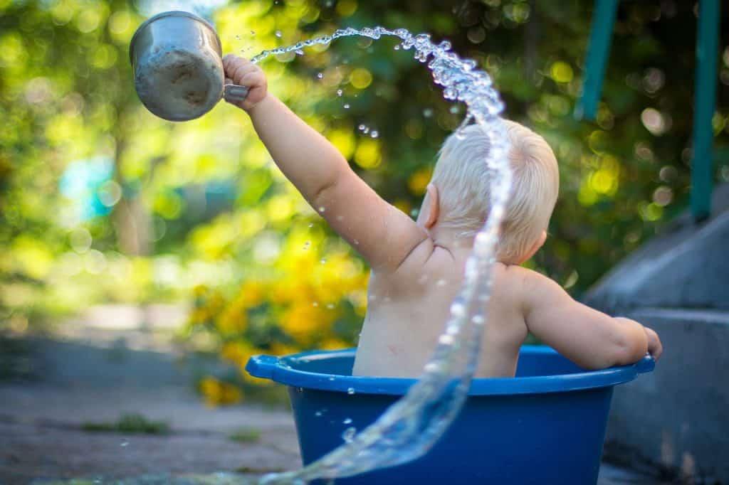 Imagem de bebê tomando banho de caneca.