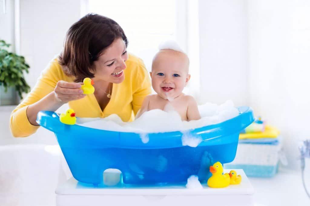 Imagem de pessoa dando banho em um bebê.