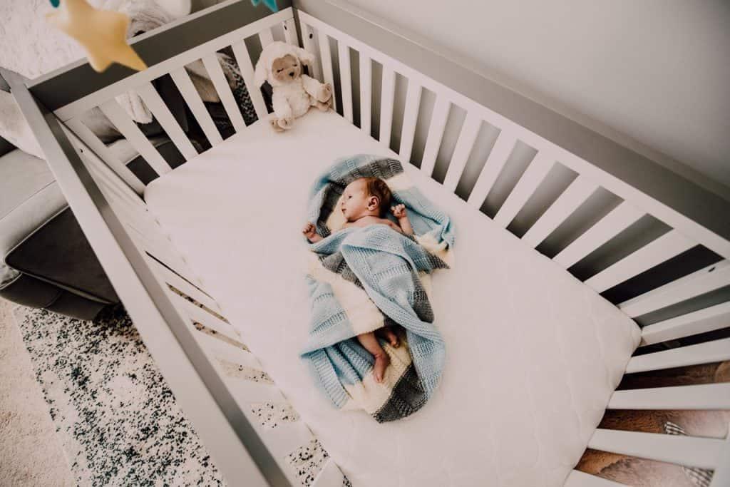 Foto mostra um bebê recém-nascido envolvido por uma manta. Ele está deitado em um berço grande. No canto superior direito há uma ovelha de pelúcia.