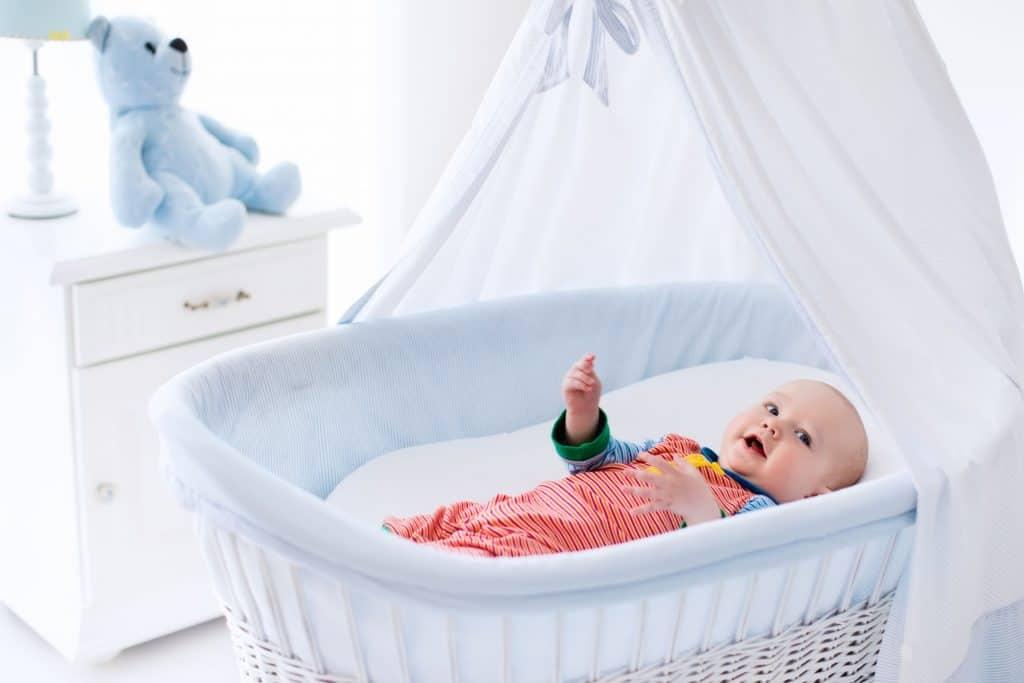 Bebê em berço com mosquiteiro.