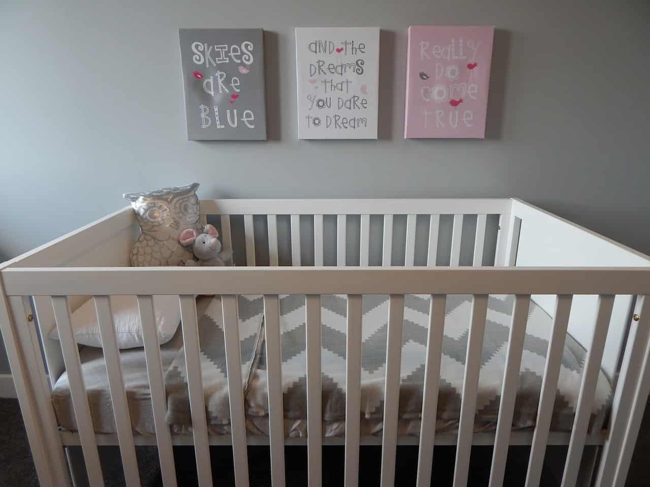 Foto mostra um berço branco vazio. Ele está preparado com lençol, travesseiro e brinquedos. Na parede atrás dele, existem três quadros.