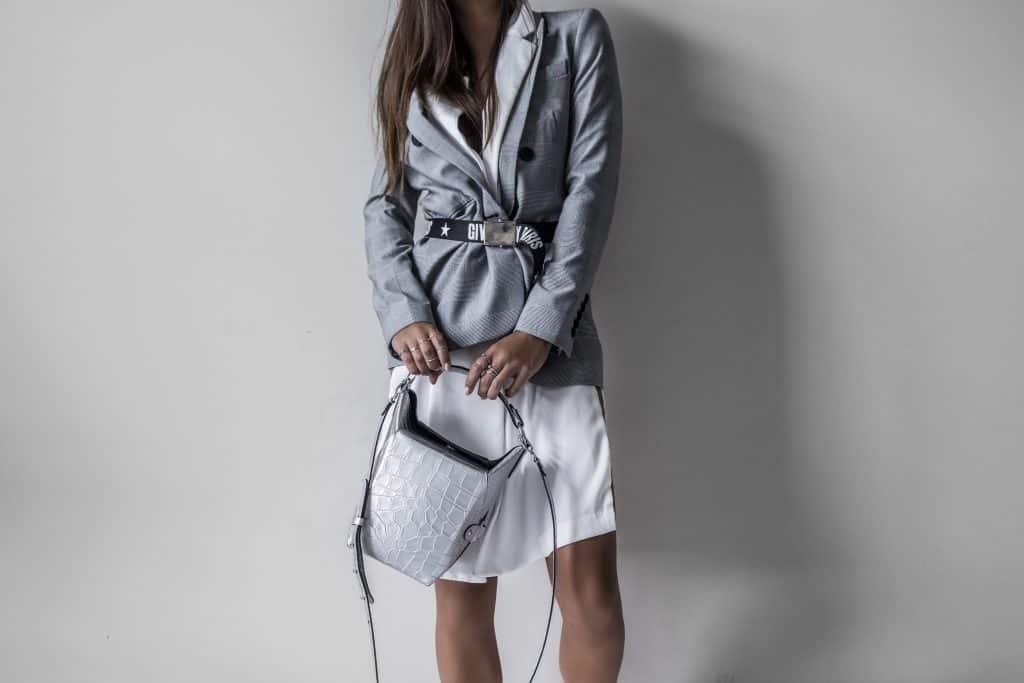 Mulher com blazer, saia e cinto.