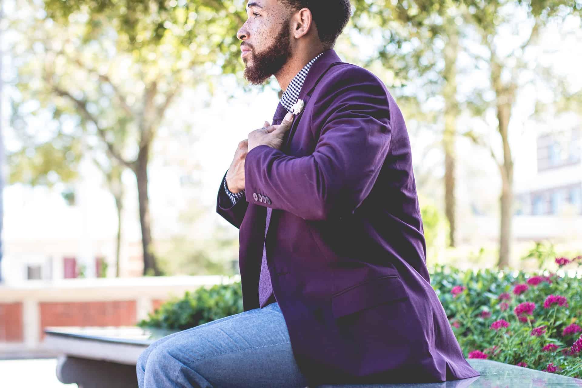 Um homem sentado de perfil arrumando seu blazer roxo.
