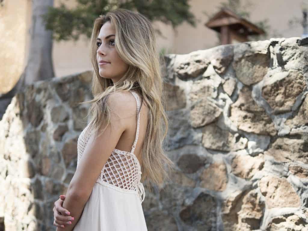 Na foto uma mulher de lado usando um vestido branco de alças.