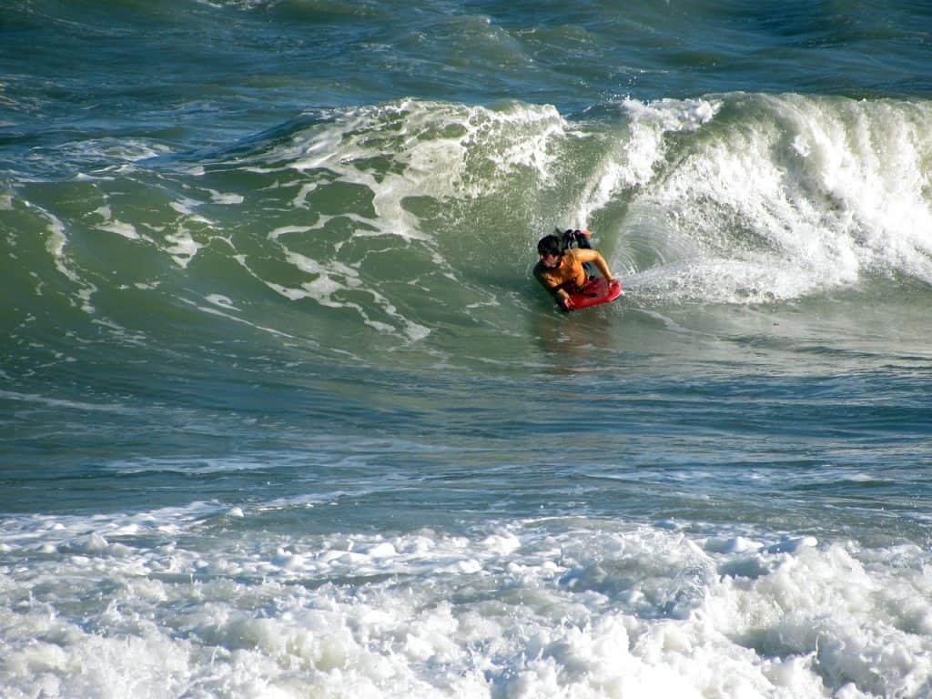 Imagem mostra um bodyboarder deslizando por uma onda média.